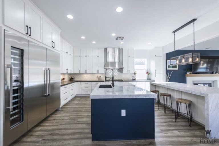 white kitchen with blue island in upgraded house