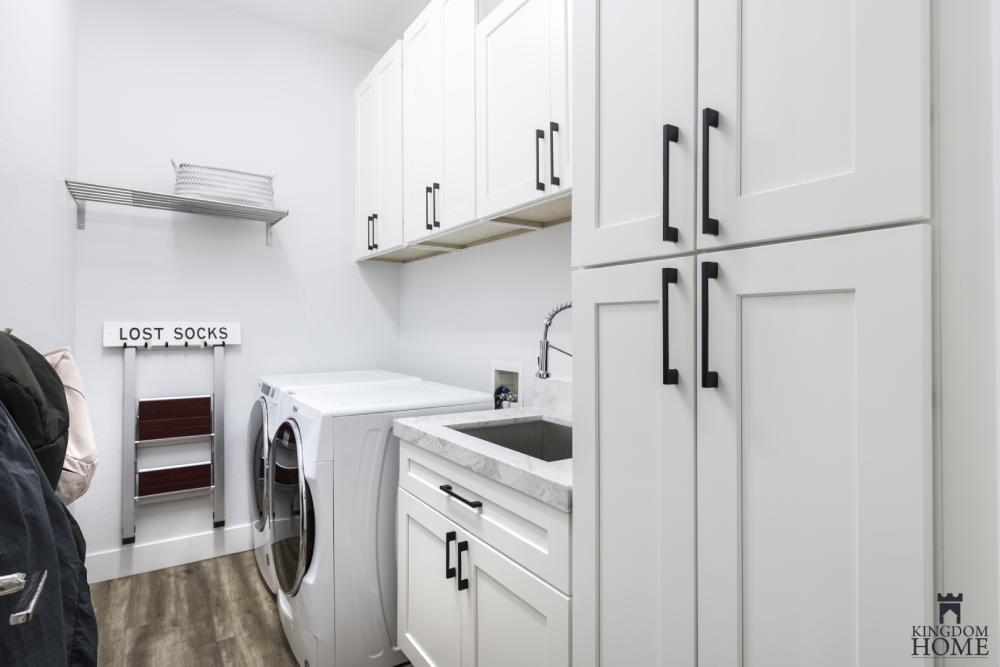 all-white laundry room in upgraded house