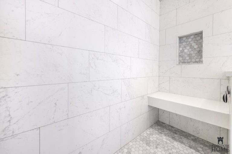 tiled master shower with seat in renovated home